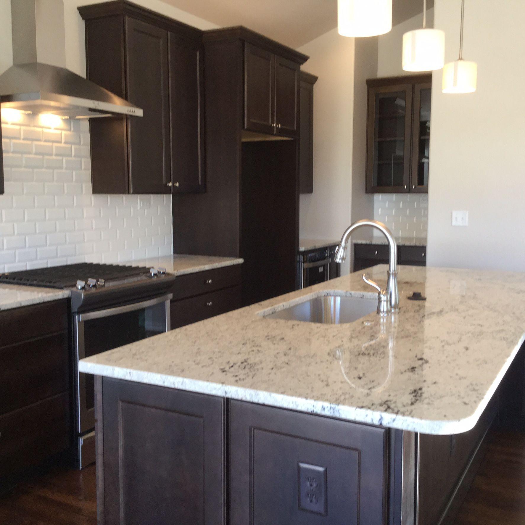 Gourmet kitchen features colonial white granite espresso maple