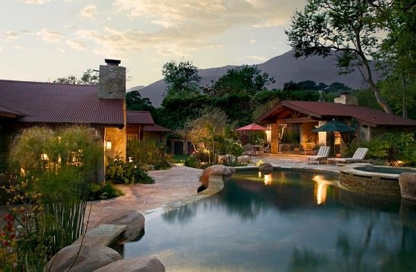 Corrugated metal roofing in the backyard adds to the dreamy appeal of this natural pool setting