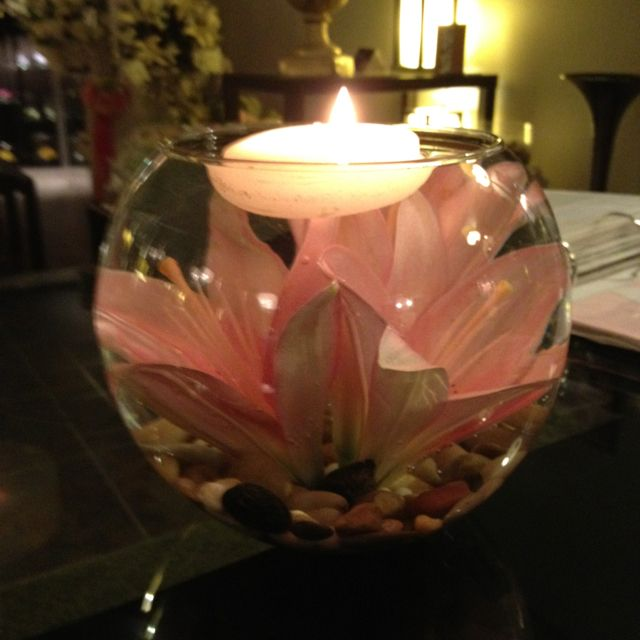 lilies in bowl centerpieces with rocks and floating candles