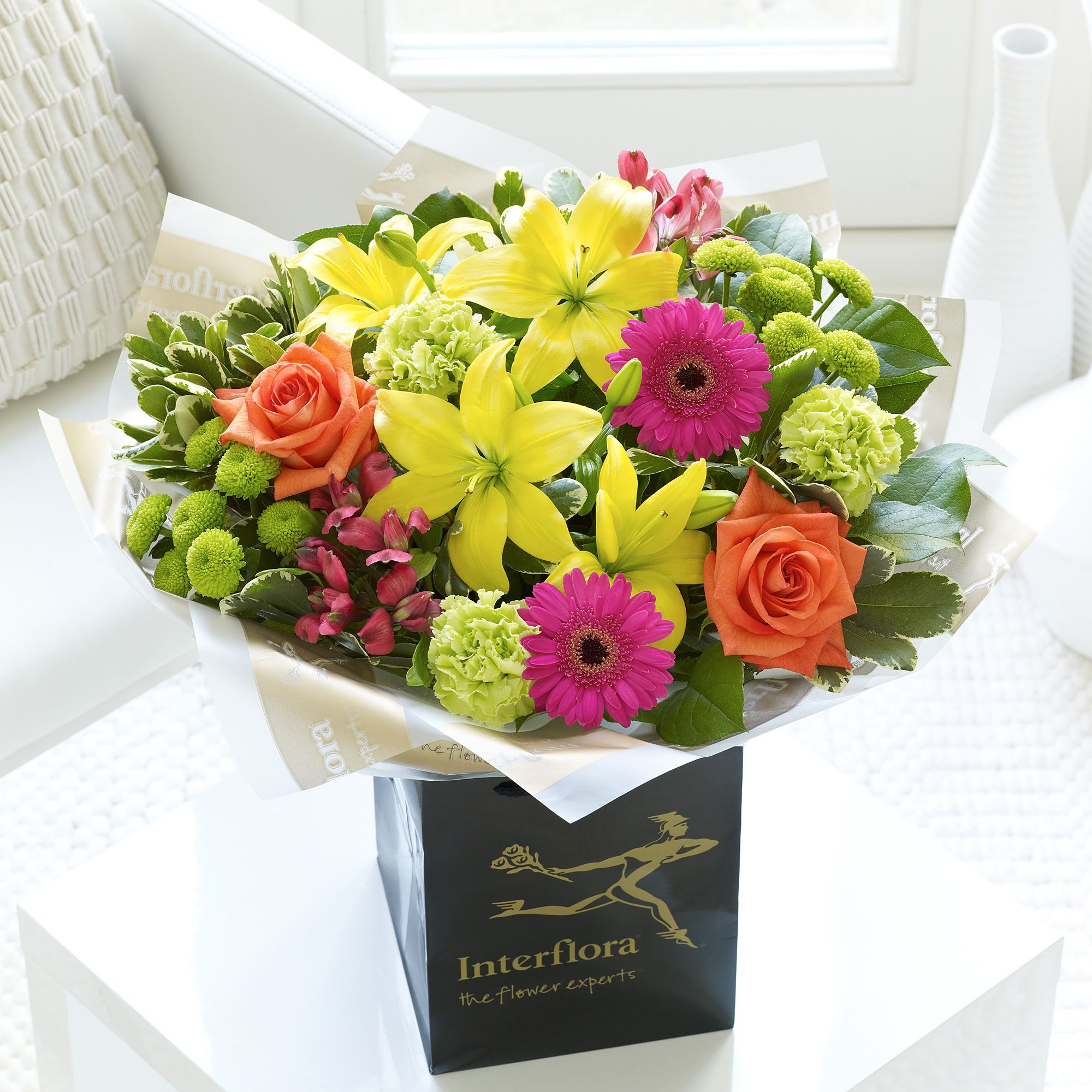 Our vibrant handtied is bursting with colour from orange roses to