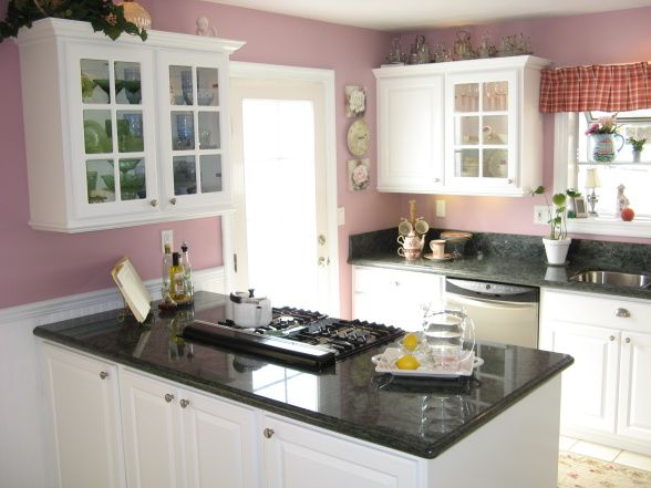 Love the open, roomy feel of an otherwise compact kitchen. Pink walls/ White