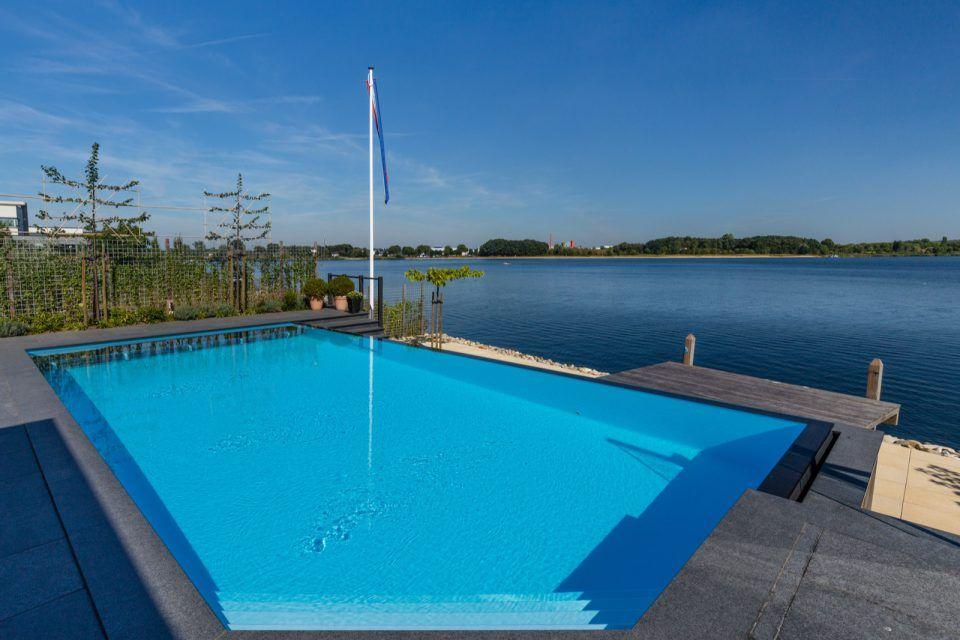 Luxe buitenzwembad infinity pool met overloopgoot en natuurstenen