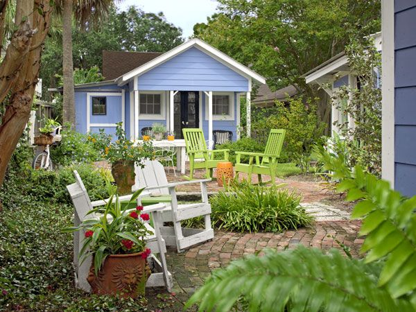 "Multiple gathering spots make a small yard seem spacious. Coslick turned around this sliver of green by painting the guest shed her own Beach House Blue, putting down paths of vintage brick and adding a table and chairs, lime-green rockers, and Adirondack seating in inviting arrays. Now it's an envy spot for friends who once thought she was crazy to take on this house. ""I just knew I could do something with it,"" she says. And she did."