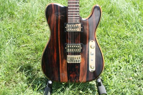 """This is a great example of custom building. Not your normal T-style guitar. This one is sleek and MEAN. Specs: 26.5"""" scale length Body: white limba core, macassar ebony back and top neck: 5-piece flamed maple/mahogany/walnut, macassar ebony fretboard gold Hipshot Products Inc bridge and locking tuners Bare Knuckle Pickups Juggernauts"""