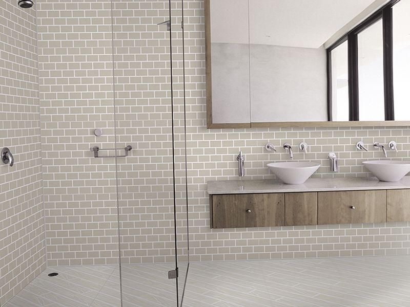 Medicine cabinet surrounded by wood frame that also opens to reveal hidden storage. Floating vanity with natural wood drawers. brick porcelain tile by Ornamenta - Ivory. Available through Stonesource