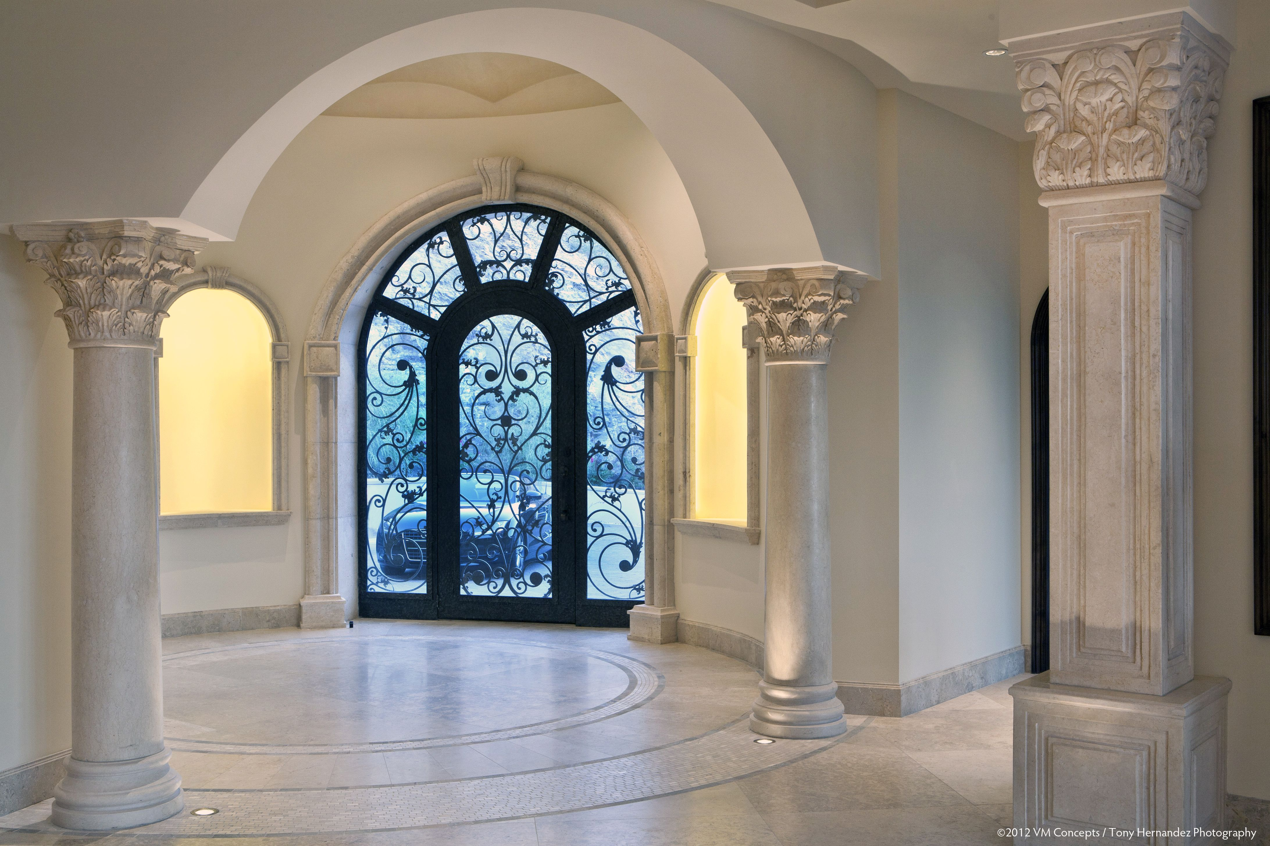 This unique and inviting front entrance to the home in Paradise Valley, AZ sets the tone for the entire European inspired home. Intricate iron work embellishes the door and windows in contrast with the light stone carvings on the interior columns. Designed by VM Concept in Scottsdale, AZ.