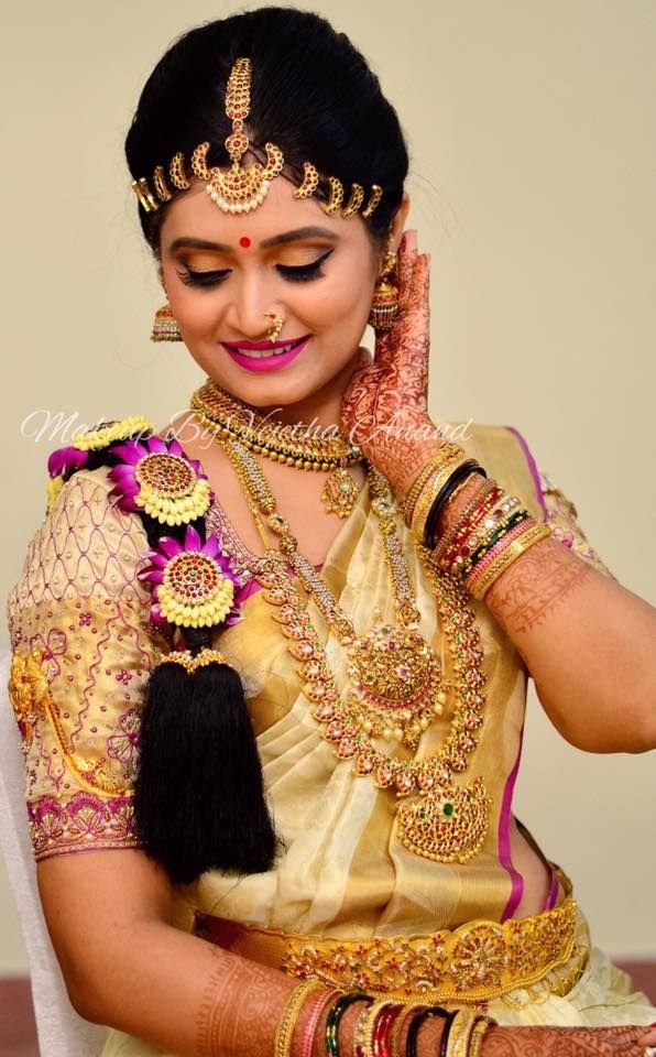 Pavithra looks breathtaking for her muhurtam. Makeup and hairstyle by Vejetha for Swank Studio. Berry lips. Maang tikka. South Indian bride. Eye makeup. Bridal jewelry. Bridal hair. Silk sari. Bridal Saree Blouse Design. Indian Bridal Makeup. Indian Bride. Gold Jewellery. Statement Blouse. Tamil bride. Telugu bride. Kannada bride. Hindu bride. Malayalee bride. Find us at https://www.facebook.com/SwankStudioBangalore