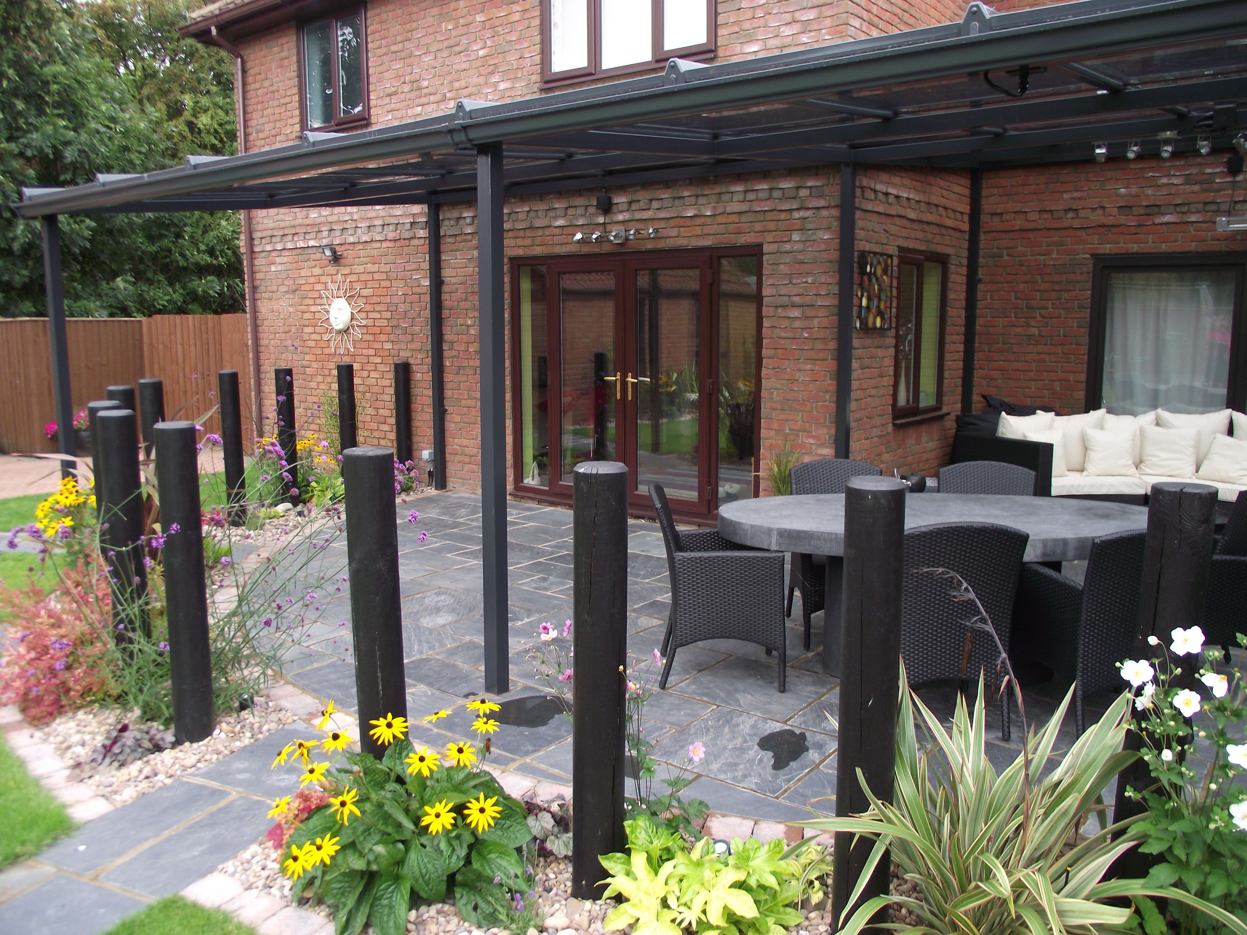 This garden has black slate patio with a roof plus a pole fence so