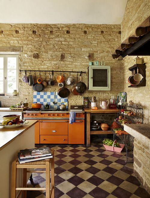Rustic farmhouse kitchen- I love the stone walls and wood stove with barrel tile exhaust hood/vent.