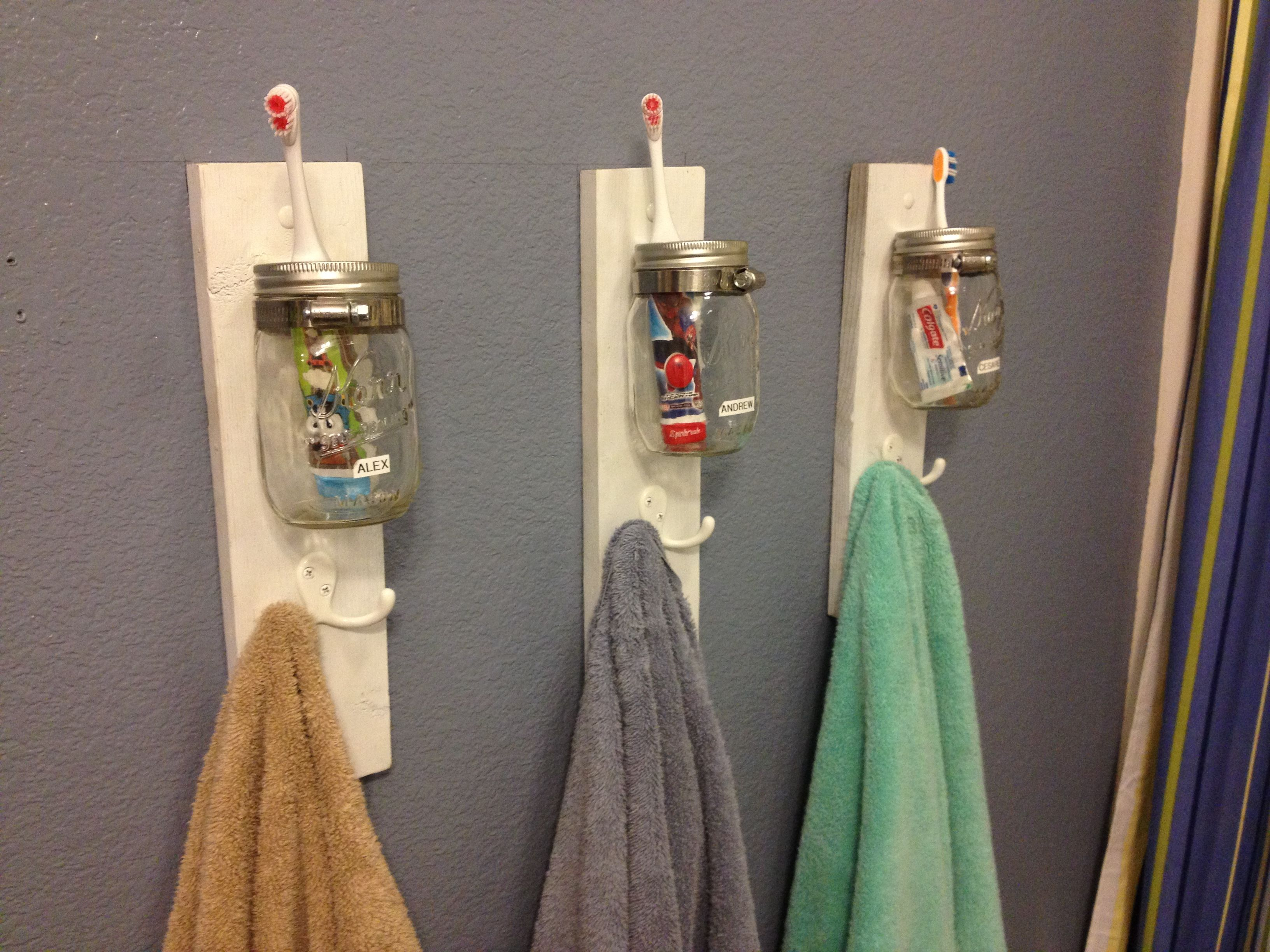 Mason jars for toothbrush holders held on a board with a ...