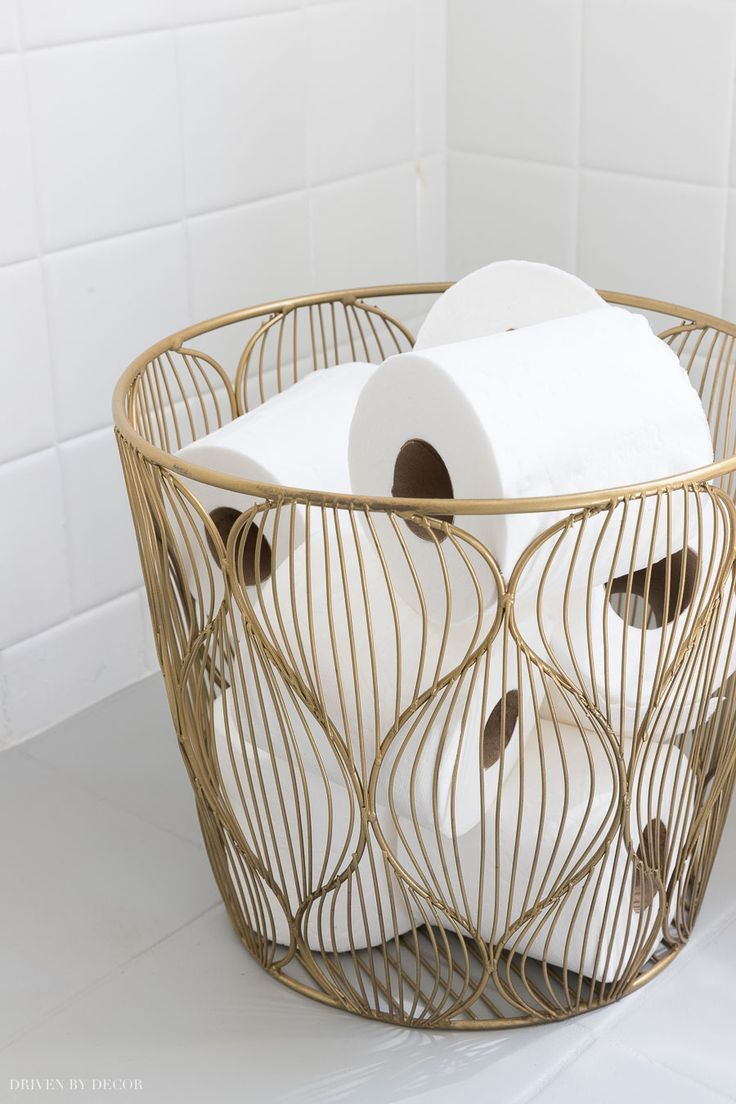This small gold wire basket is perfect for holding extra rolls of toilet paper…