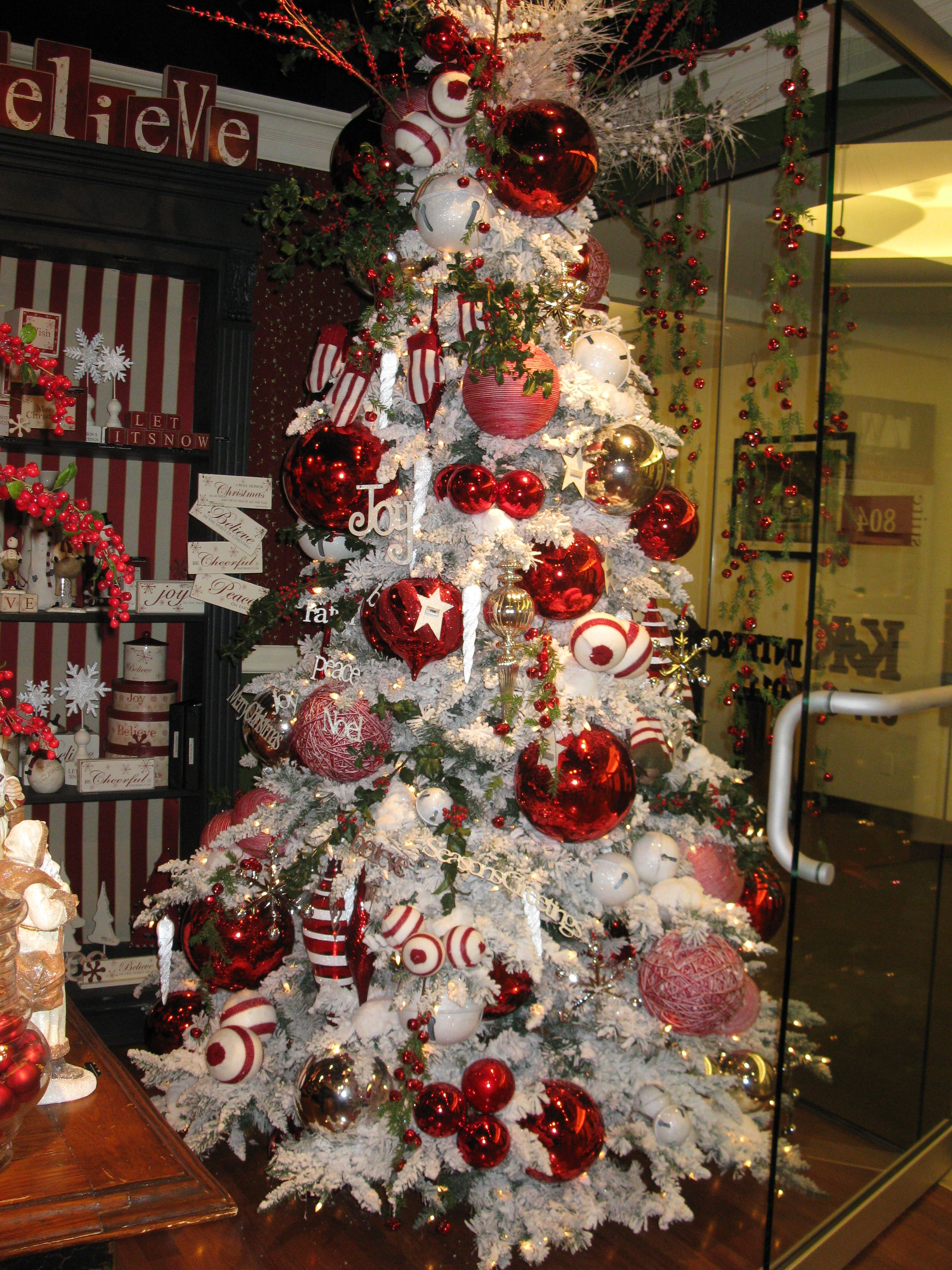 Flocked Christmas tree with oversized ornaments.