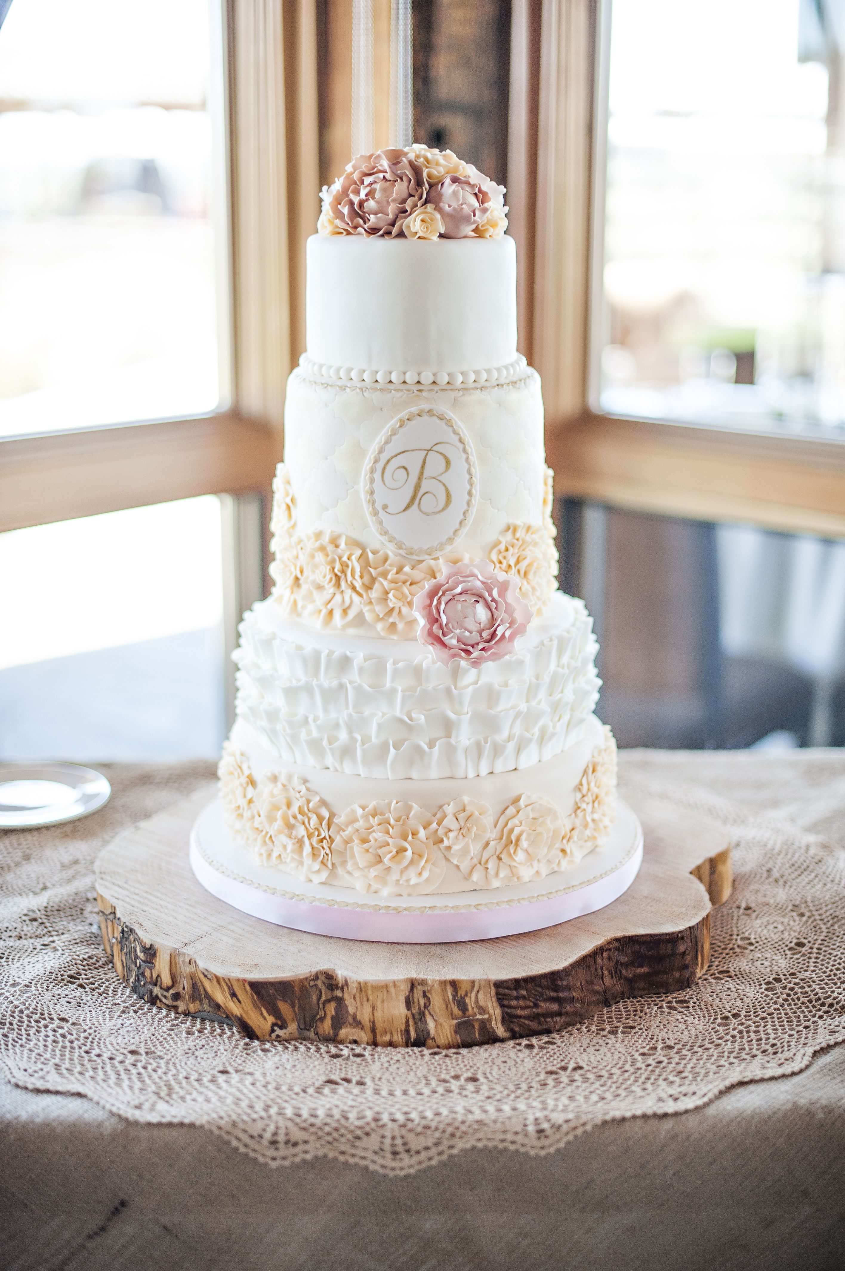 Romantic wedding cake with lots of ruffles and sugar peonies and a ...