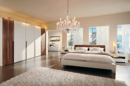 very simple and very clean-a nice bed with very clean and crisp sheets/bedding, and a fluffy white rug. the chandelier is also a nice touch.