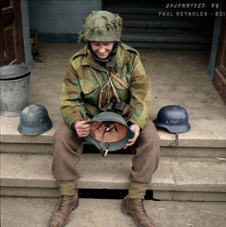 Regimental Sergeant Major Evans of the 12th Battalion, The Devonshire Regiment examines captured German helmets in Hamminkeln, Germany, March 25, 1945.