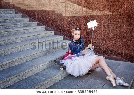 Girl listening to music on headphones. Sweet ballerina makes hipster selfie phone on selfie stick. A girl wearing tutu, ballet shoes and sneakers, sunglasses. Girl riding on skateboard. Youth fashion.