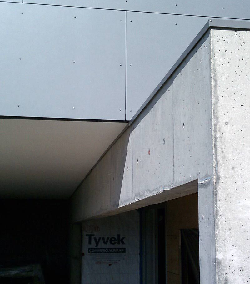 Stucco soffit at flashing over concrete wall at the for Concrete exterior walls