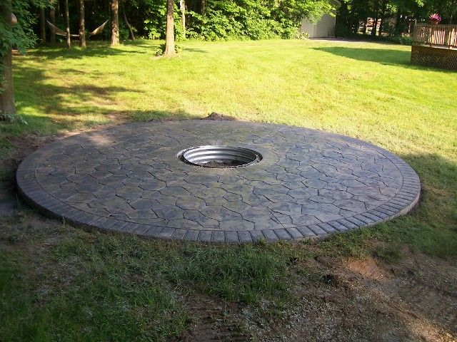 outdoor fire pit made of wood rounds from a fallen tree and rocks