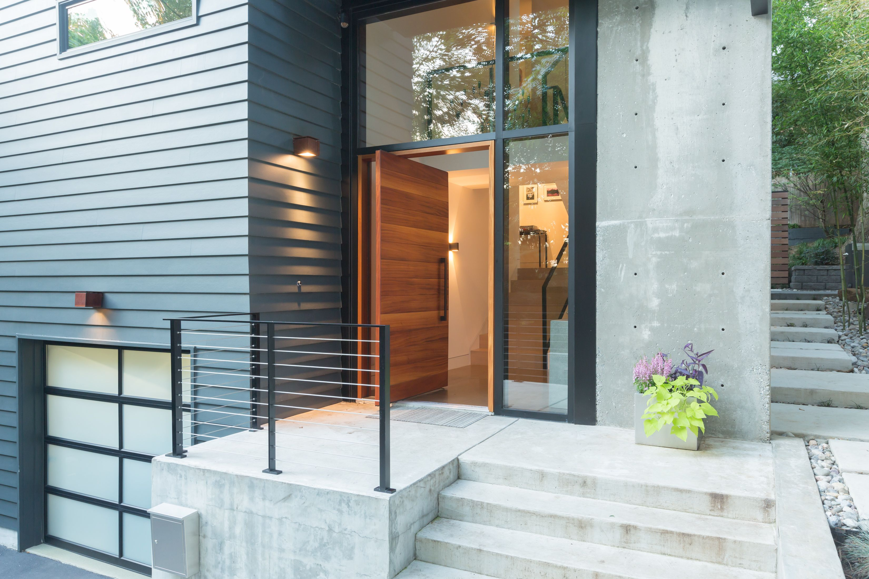 Modern house with mitered HardiePlank Artisan siding, aluminum curtain wall, board-formed concrete wall and steps, steel and cables railing, frosted glass garage doors, rusted Corten steel lights by Viabizzuno, and Sapele African Mahogany pivot door with Chant hardware and door pull in Washington DC.