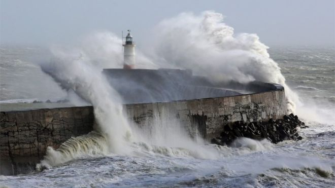 Waves crash over lighthouse in Newhaven, East Sussex