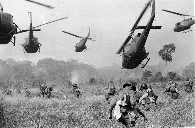 Hovering U.S. Army helicopters pour machine gun fire into a tree line to cover the advance of South Vietnamese ground troops in March 1965. The troops were moving to attack a Viet Cong camp northwest of Saigon near the Cambodian border