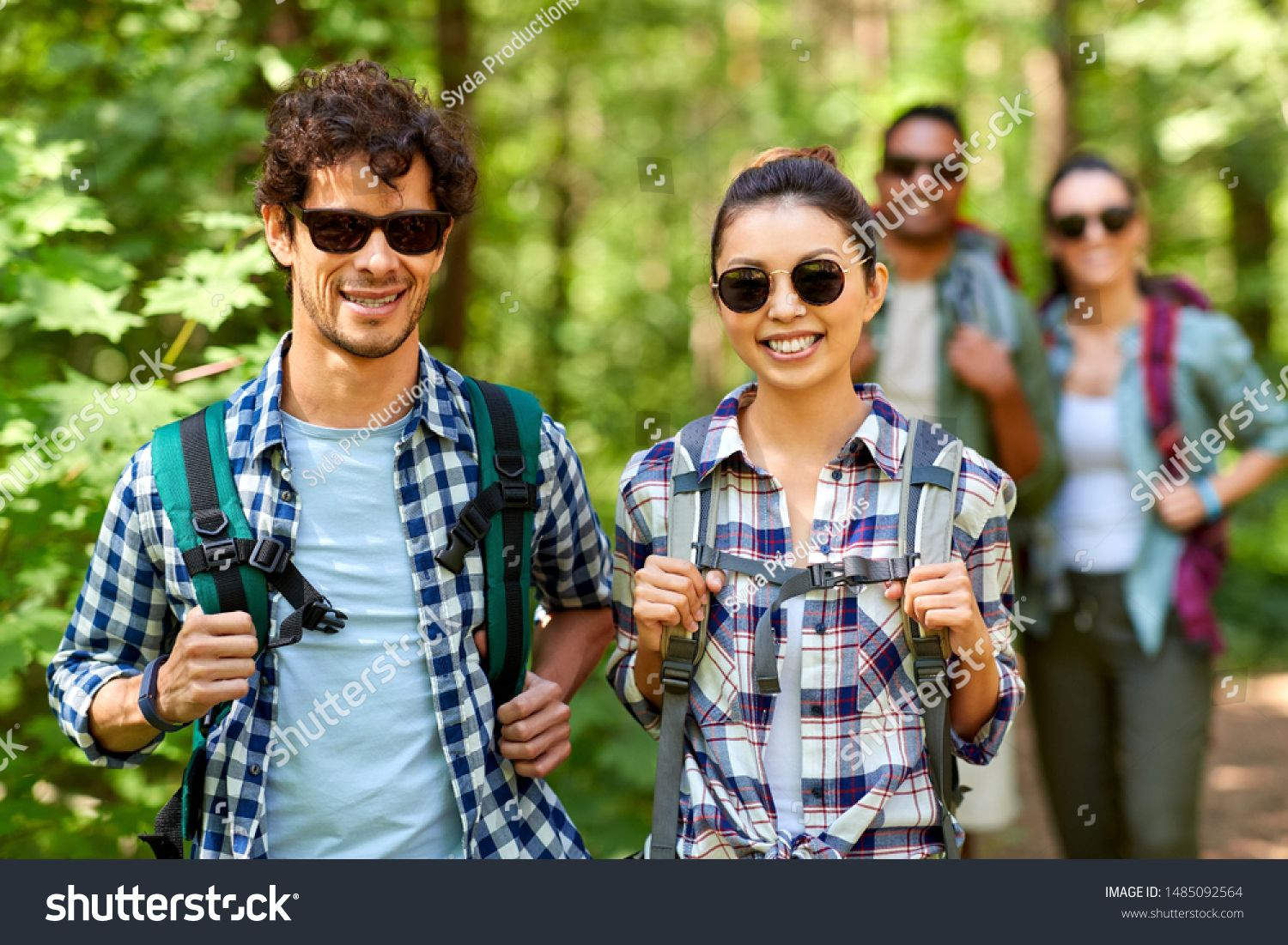 travel tourism hike and people concept  group of friends walking with backpacks in forest