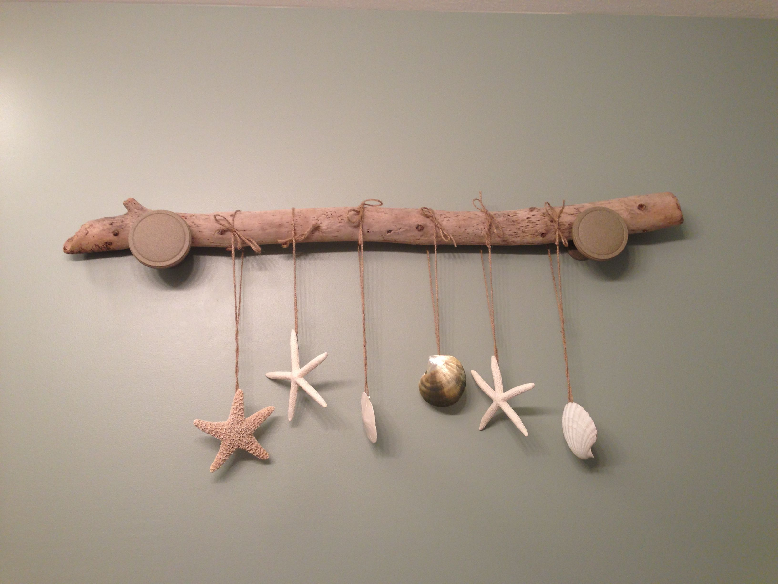Driftwood project.... Dried out drift wood about 4 ft long, variety of shells and starfish and sand dollars with hooks/wire loops hot glued to the back, twine to tie them on to the wood, and curtain rod holders spray painted a neutral color to match the wood