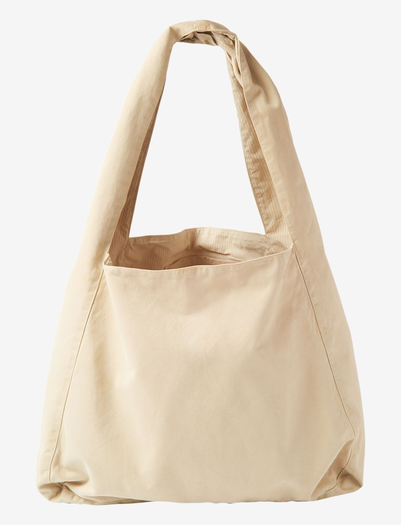 Oversized shopper in a comfortable, peachy cotton twill. Wide pleated straps and stitched-through internal pocket. Large, flat base. Lined in a garment-dyed stripe.