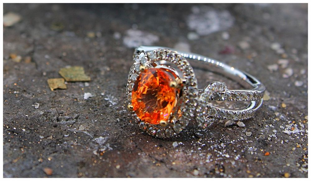 Spessartite ring with diamond halo:  This 9 x 7mm spessartite glows like a comet streaking through the midnight sky. In 14K white gold, the bright orange stone is held in a four-prong setting with a diamond halo.  Diamonds continue down the split shank.