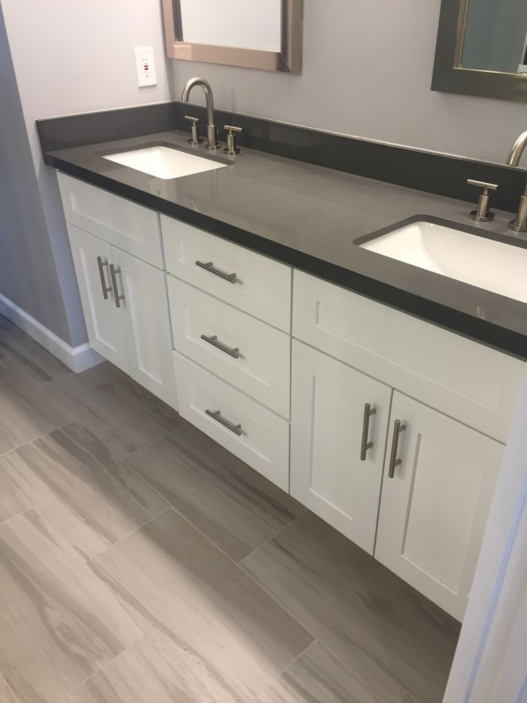 This bathroom includes J K s white shaker style cabinets which showcase the  gray quartz Countertops complete with undermount sinks. The master bathroom has black granite countertops with double