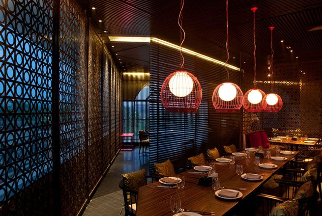 Zazen Restaurant, Chandigarh, India designed by Hirsch Bedner Associates (HBA). Lighting design by Illuminate. Tables are picked out with strong beams of light whilst the screens are accented helping to showing the interior finishes to their best effect.