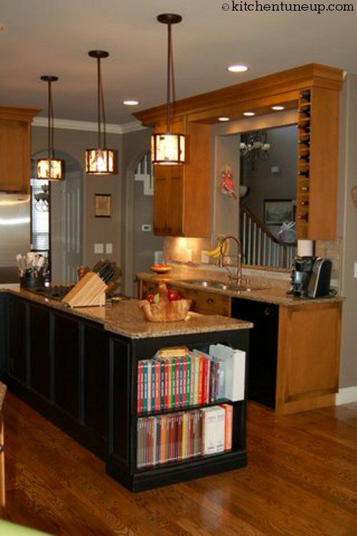 A darker colored kitchen island adds dimension to this kitchen.  The functionality of this island is also a bonus with its cook book shelf, stove and ample counter top space!