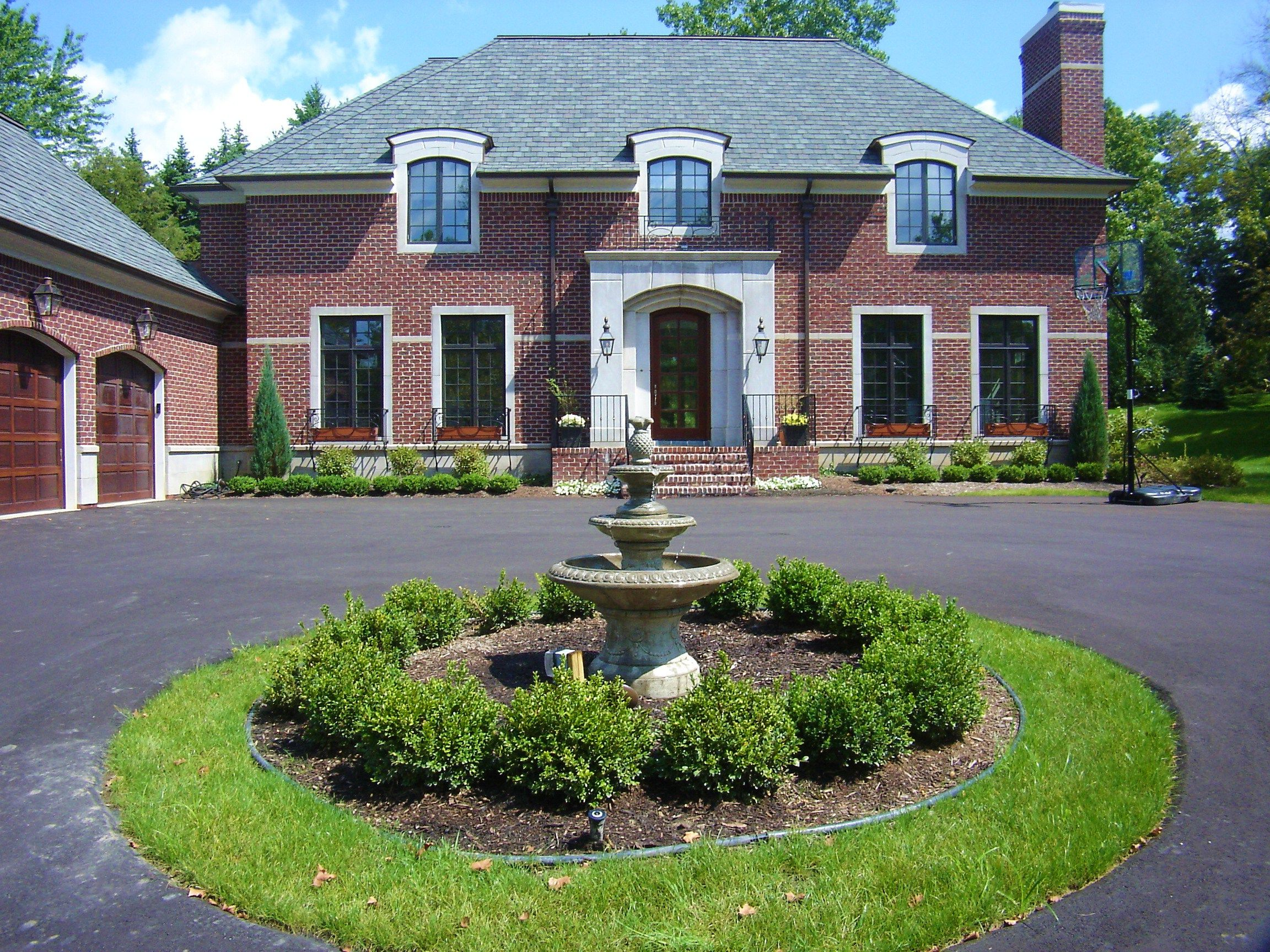 Circle driveway with boxwood hedge around water fountain for Semi circle driveway ideas