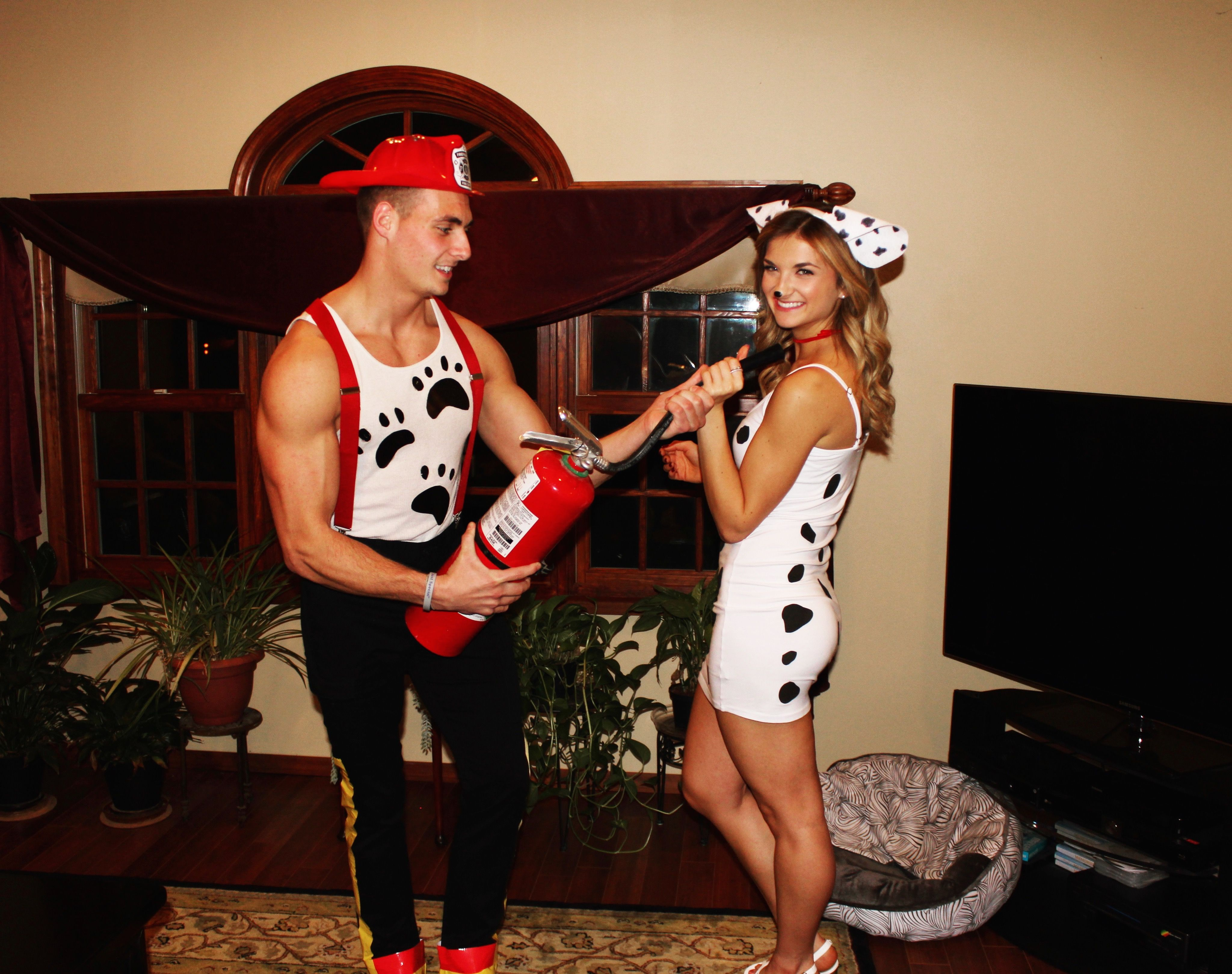 Couple halloween costume firefighter and Dalmatian dog