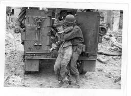 An American infantryman picks up a wounded German soldier on the road to St. Lo…