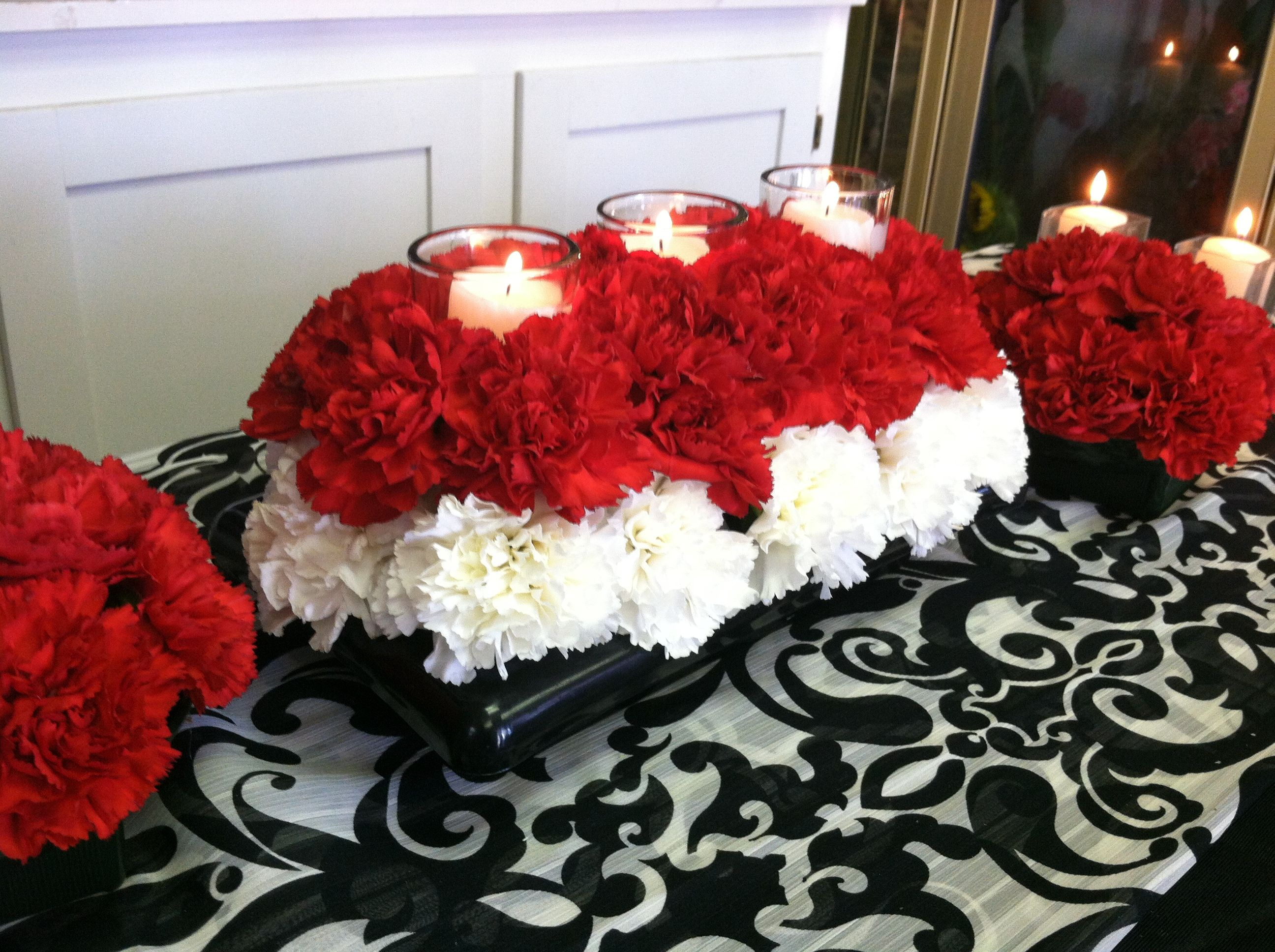 Grouping of red and white carnation centerpieces with