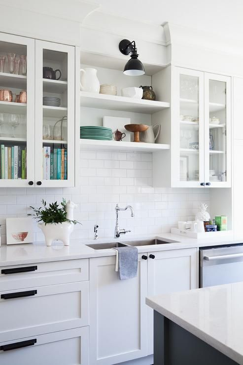 A black down-lit sconce is mounted above off-white shelves ...