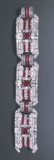 AN ART DECO RUBY AND DIAMOND BRACELET The wide band of geometric design, composed of three openwork old European-cut diamond and calibré-cut ruby panels, each centering upon a circular or oval-cut ruby, enhanced by baguette-cut diamond detail, joined by arched baguette-cut diamond and calibré-cut ruby links, mounted in platinum, (three rubies deficient), circa 1935, 7¾ ins.