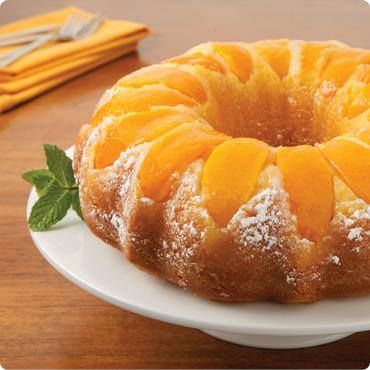 Double Peach Pound Cake ¼ cup all-purpose flour, divided 2 can (15oz.ea) Sliced Cling Peaches ⅓ cup vegetable oil 4 egg whites [or 2 whole eggs] ½ tsp. Almond extract 1 pkg. yellow cake mix, 15.25 oz. ¼ cup powdered sugar Preheat 325° F. Coat a bundt pan with non-stick cooking spray, and dust with flour. Arrange 1 can of drained peaches on bottom of pan. Mix on medium, beat oil, egg, almond extract & 1 can of peaches with syrup, in large bowl 30 seconds. Add cake mix, beat. Bake 60-65 min