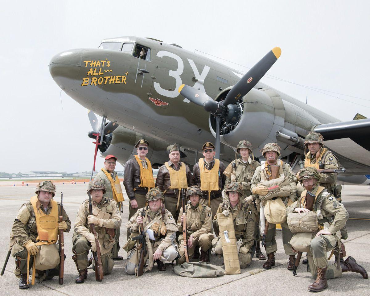 World War II reenactors pose in front of a Douglas C47