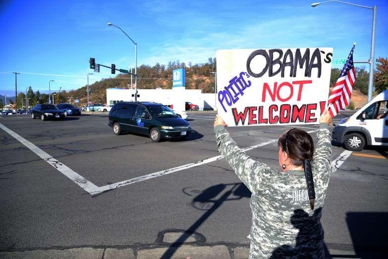 Demonstrators wait outside of Roseburg Regional Airport for President Barack Obama's arrival, Friday... - AP Photo/Ryan Kang