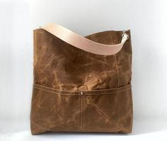 Our waxed canvas bucket bag is durable, lightweight and a breeze to carry. This rugged, natural canvas bag in Saddle Brown ages beautifully and looks better with a little wear and tear; becoming softer and more creased with use; giving it that sought after well-worn, lived in look. Our bucket tote has an easy-carry-shape and includes 5 slip pockets (2 outside and 3 inside) as well as a large interior zippered pocket. A double-wide, natural leather strap and nickel plated hardware complete…