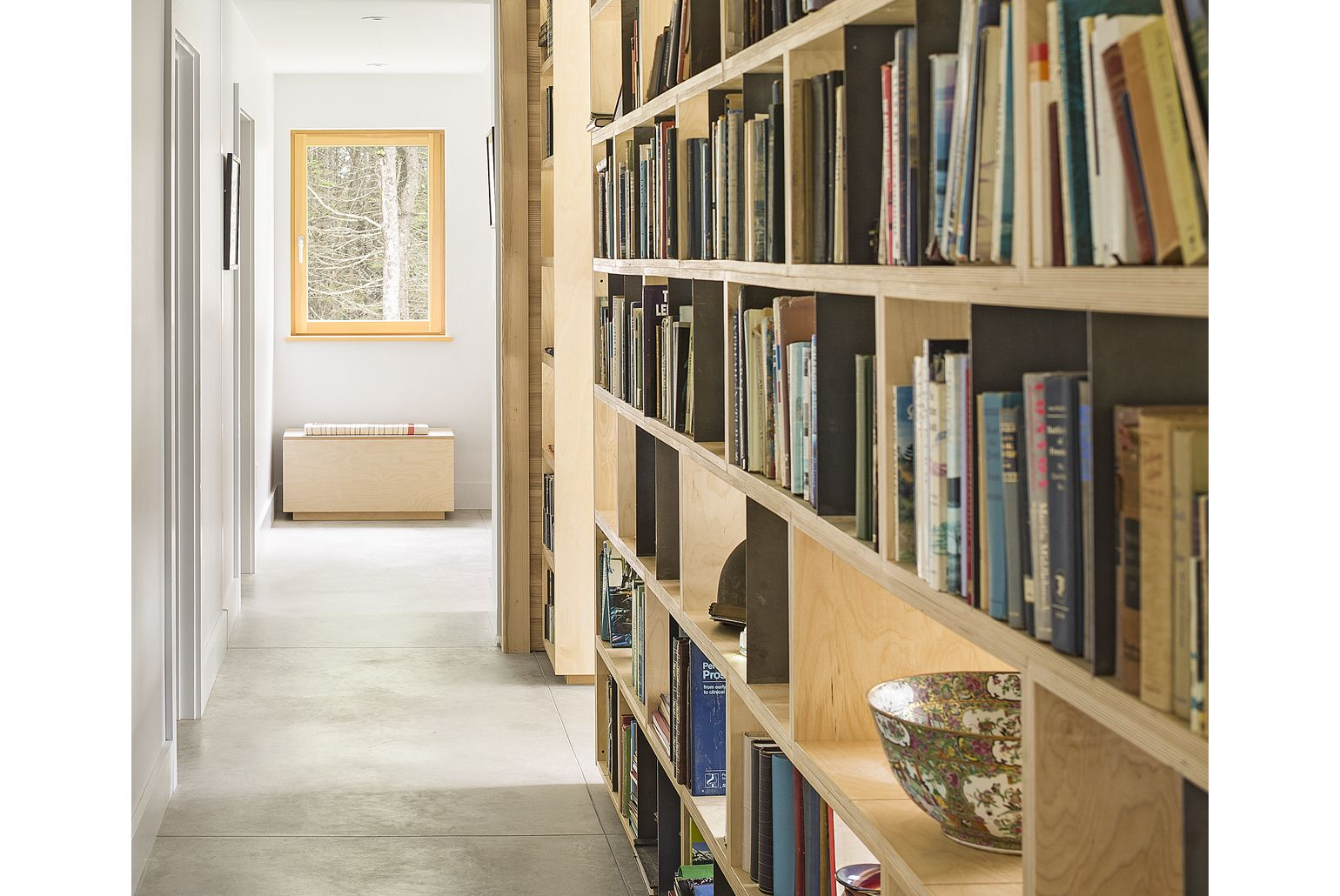 The custom bookcase allows light to pass through and into the hall