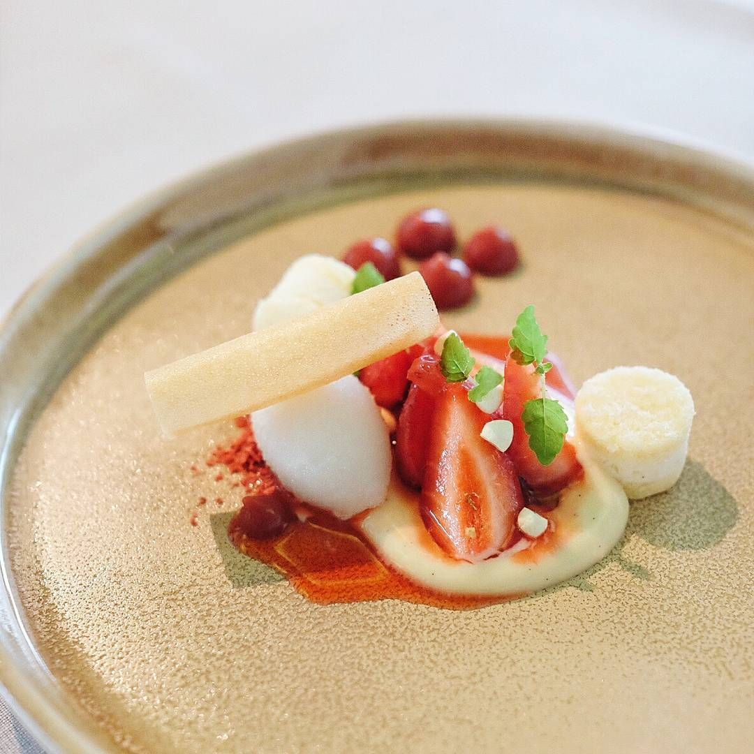 """Fresh strawberries, vanilla parfait, spiced coconut sorbet, Chinese """"egg roll"""" cookie, ruby red consomme."""