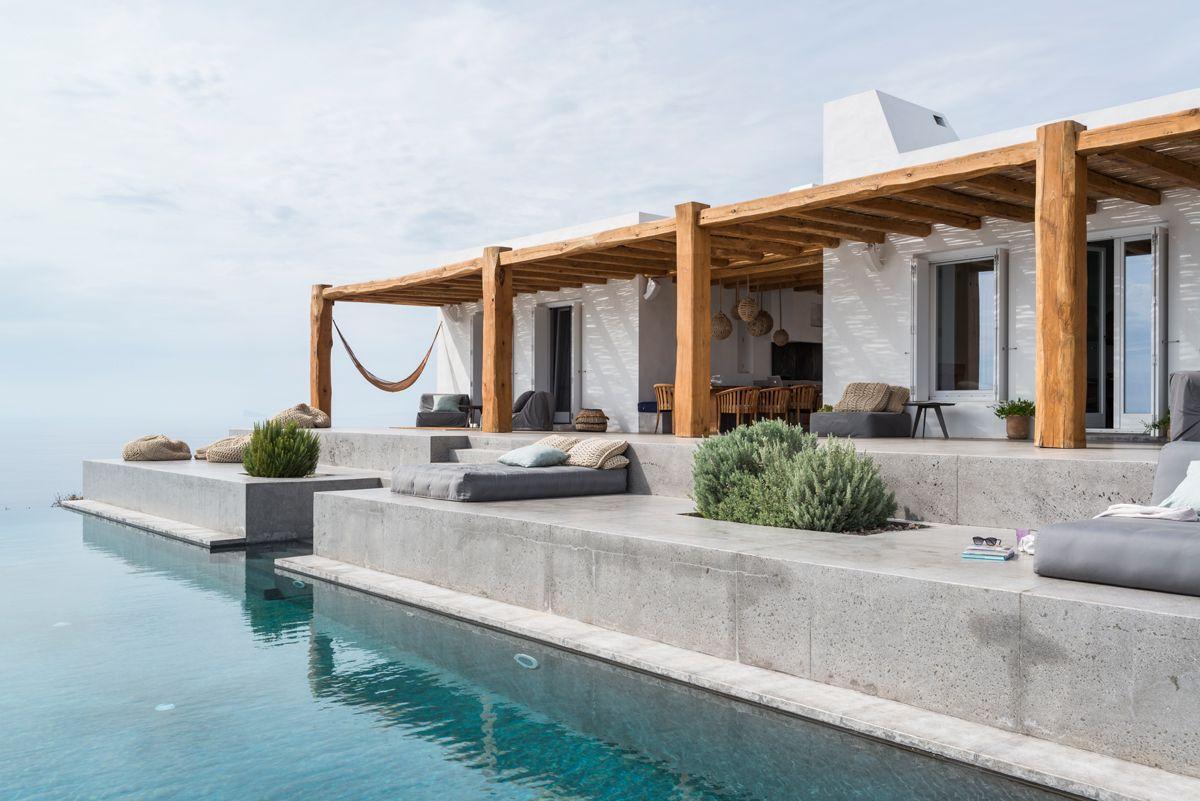 Sull'isola di Syros nelle Cicladi la casa vacanze di Jorge Tsiogkas: una villa con interni rustici, un pergolato e una piscina che si fonde col mare