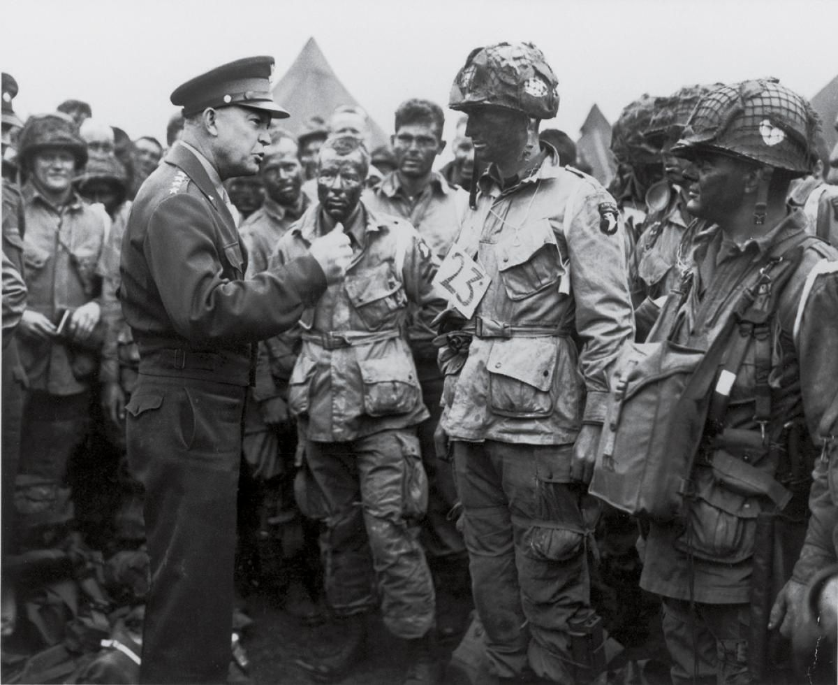 U.S. 101st Airborne Division troops gather around commander General Dwight Eisenhower (l.) while he gives them a pep talk prior to the D-Day invasion of Nazi-occupied Europe.