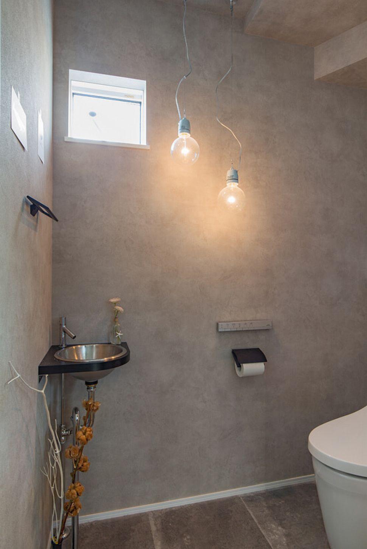 落ち着いたモノトーンの色合いのシンプルなトイレ 印象的なペンダント