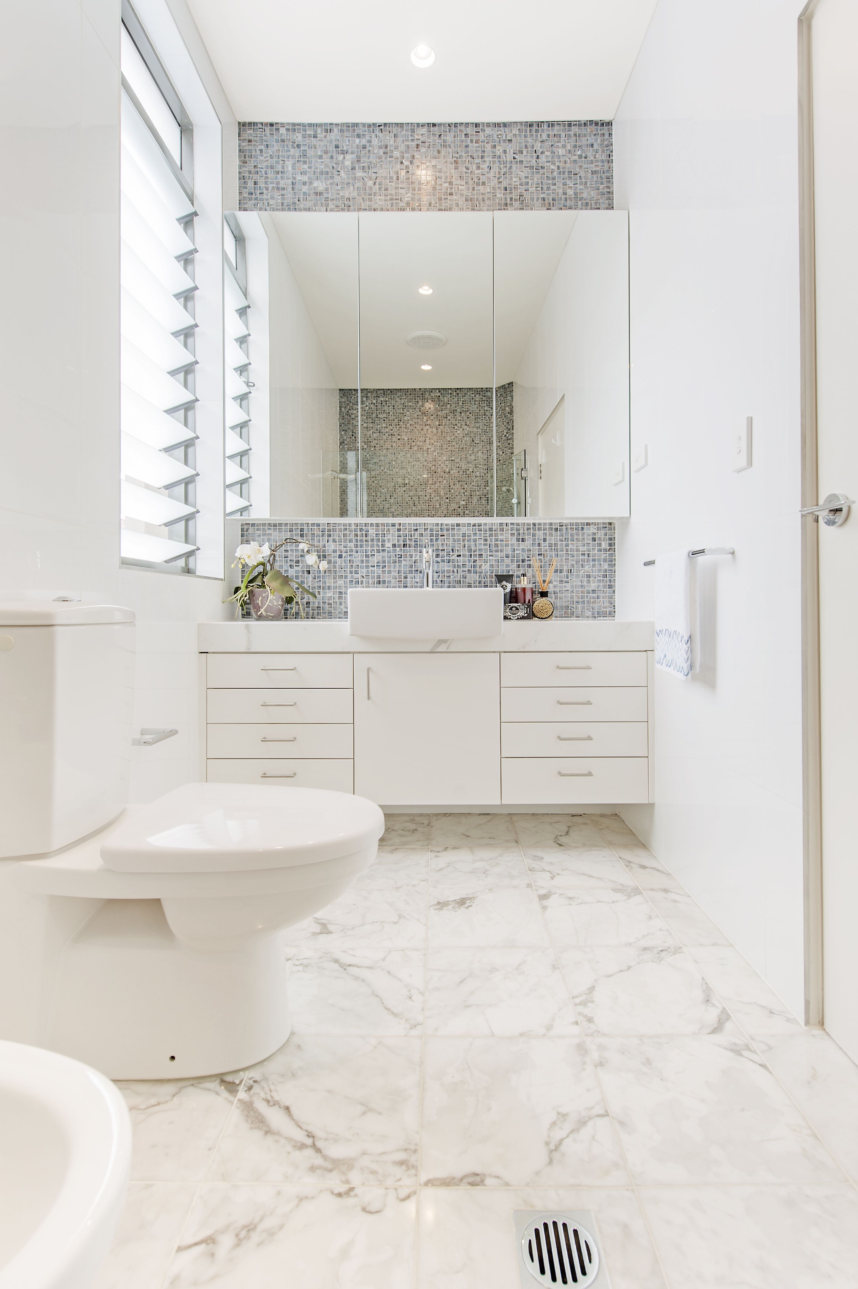 White bathroom with square basin, marble floor tiles, mosaic ...