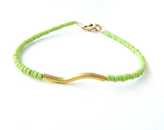 Neon green beaded tiny bracelet with gold wavy tube by Aperitto, $10.00
