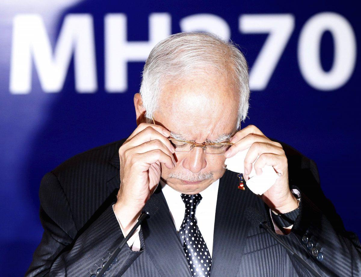 Prime Minister Datuk Seri Najib Razak adjusts his glasses before confirming the debris found on ...